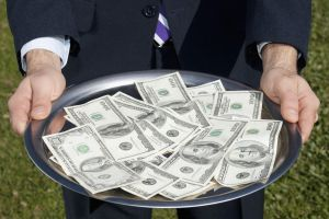 Businessman holding US currency notes on a plate