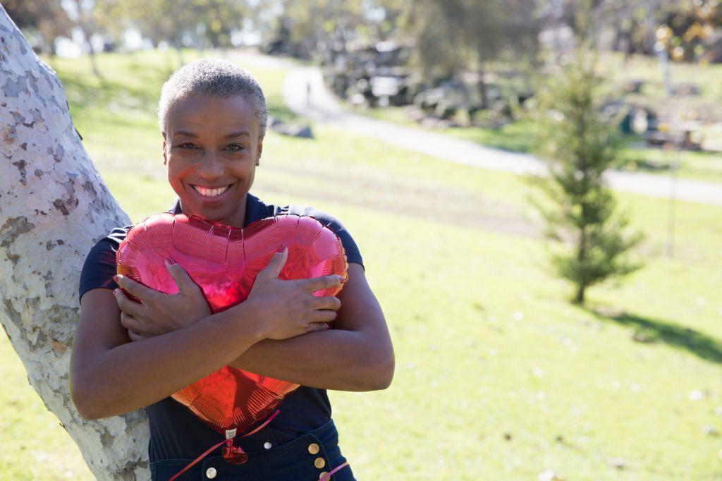 Mature woman hugging red heart-shaped balloon, Hahn Park, Los Angeles, California, USA