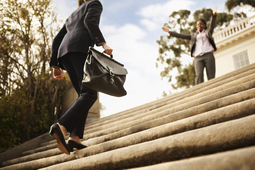 Businesswoman walking up stairs toward co-worker