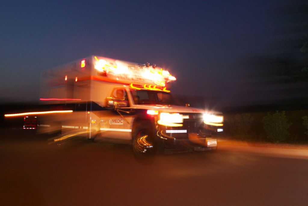 Motion blurred image of an ambulance speeding past the viewer