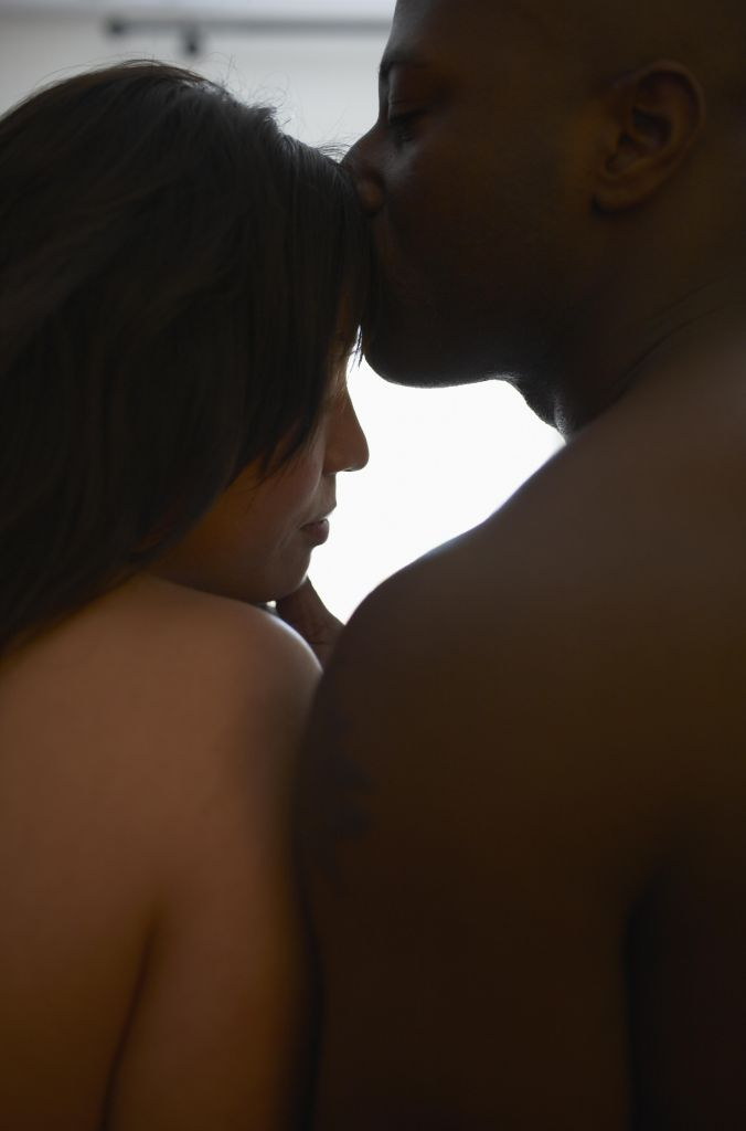 Young man kissing woman on forehead, close-up, side view