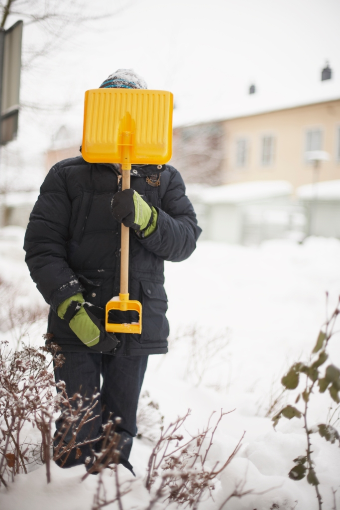 Child holding snow spade in front of face