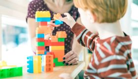 Mother and Baby Boy Playing with Colorful Blocks