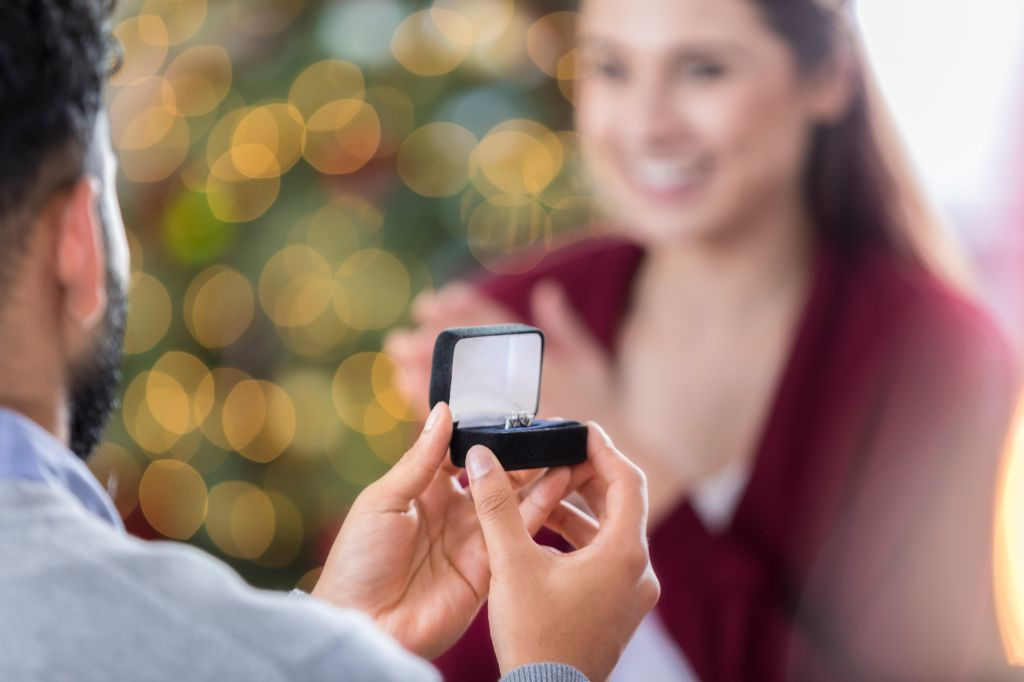 Closeup of ring box as young man proposes to girlfriend