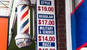 barber pole and sign in front of barber shop