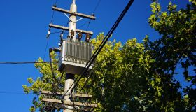 Power transformer on a concrete electricity pole against tree canopies and a clear blue sky