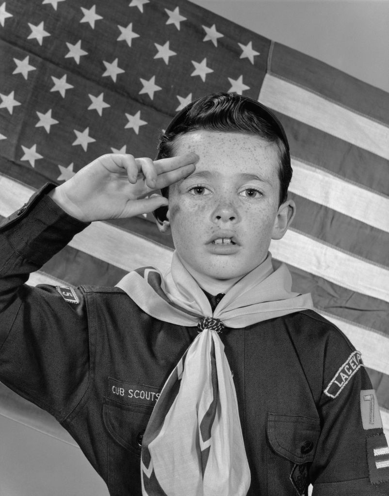 BOY SCOUT SALUTING IN FRONT OF AMERICAN FLAG