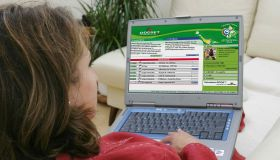 Deutschland, Internethandel, Online-Shopping, Frau sitzt zuhause auf dem Sofa und surft mit Notebook im Internet