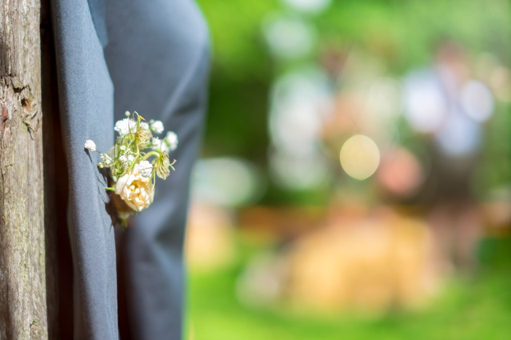 Part of a suit jacket with corsage hanging on a tree trunk.