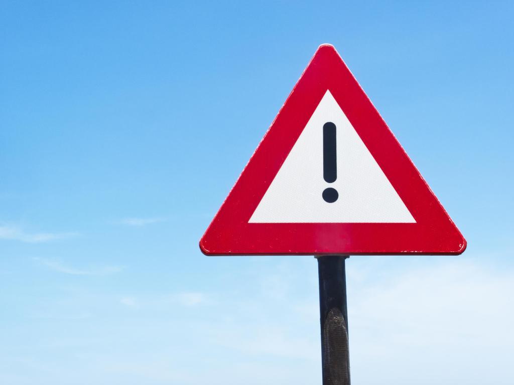 Caution road sign against blue sky