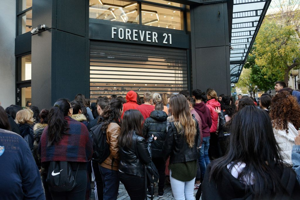 People are seen standing outside forever 21 shop as they...