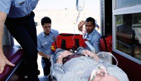 Emergency medical technicians putting patient on gurney in ambulance