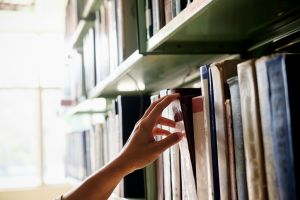 Cropped Hand Of Woman Removing Book From Bookshelf In Library