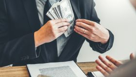 Midsection Of Agent Putting Paper Currency In Suit At Office