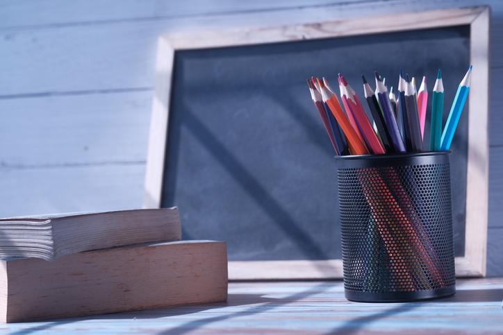 colorful pencils in a pencil pot, books and blackboard