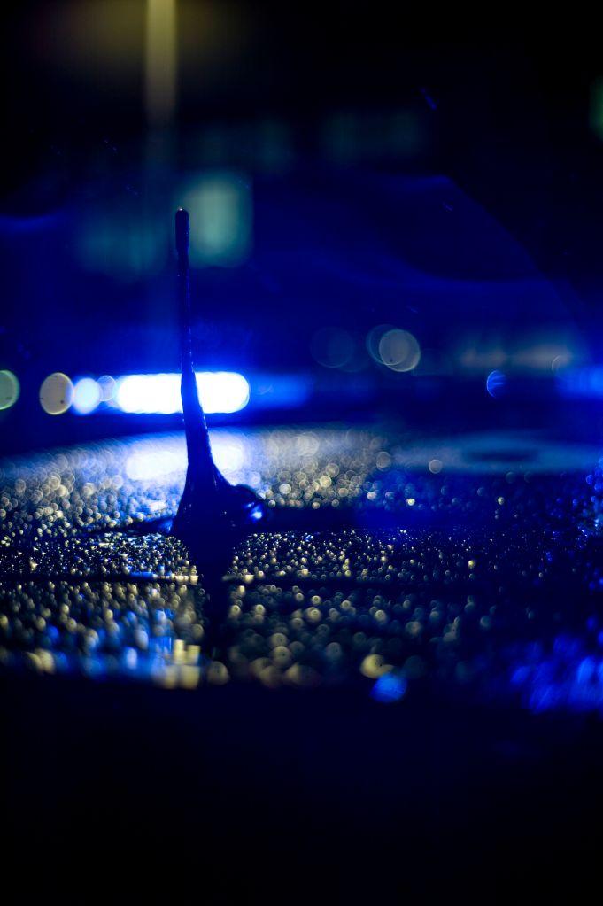 Spain, Madrid, rain falling on a police car at night