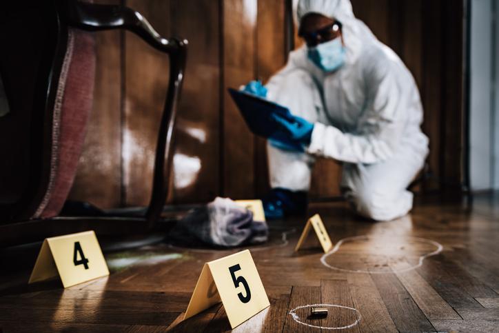 Scientist Investigating At Crime Scene