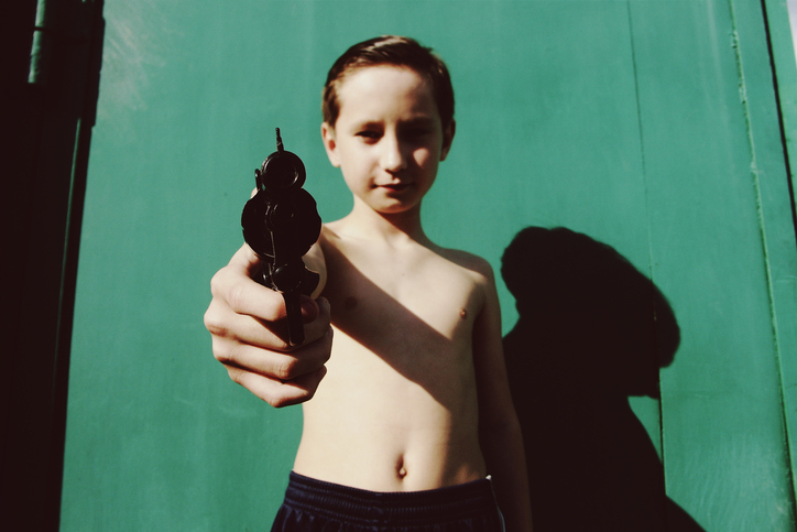 Portrait Of Shirtless Boy Holding Toy Gun Against Green Wall During Sunny Day