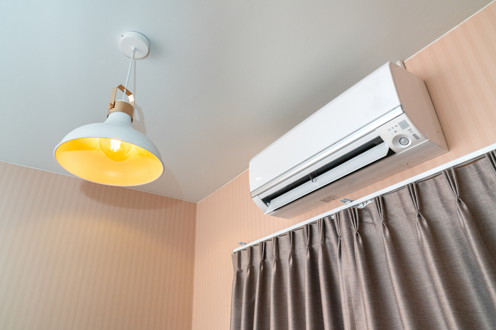 Low Angle View Of Air Conditioner By Lighting Equipment At Home