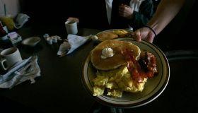 Gaby Estrella (Cq), serves Grand Slam breakfast at Denny's Restaurant in Santa Ana on the morning o