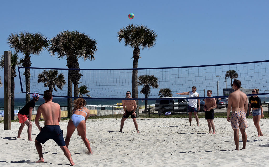 Spring breakers play volleyball during a spring break at...