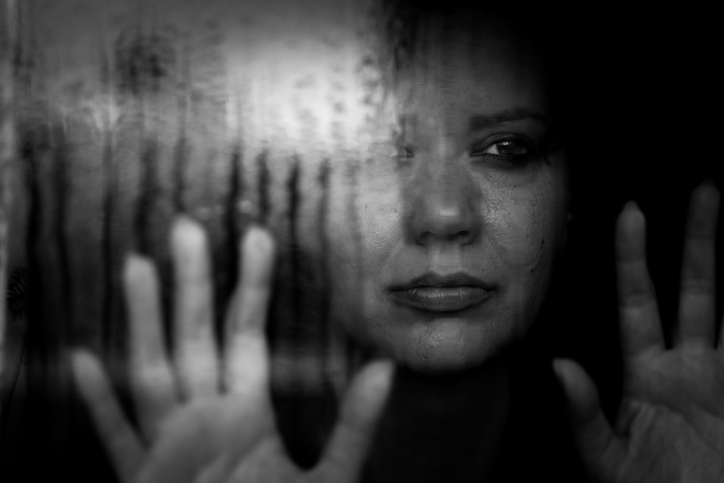 Depressed woman looking out of rainy window