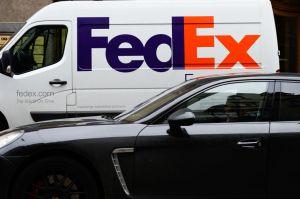 A car drives past a FedEx van in Riga...
