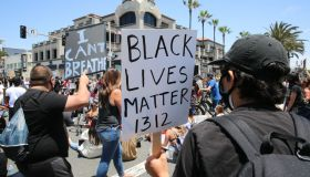 Protesters hold placards during the demonstration. The death...