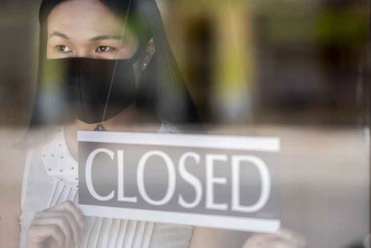 Female business owner closing her store and promoting online shopping while being closed due to COVID19.