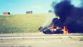 View Of Burning Car On Road Against Clear Sky