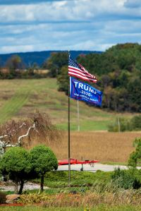 A Trump 2020 re-election flag flies below an Amrican flag in...