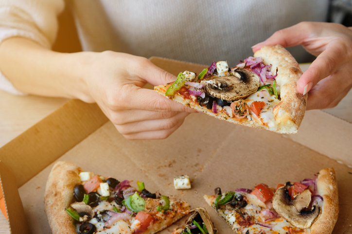 A slice of Italian Vegetable Pizza With Cheese and Mushrooms in the hands of a Girl. A Woman Takes A Slice Of Pizza And Eats It, In A Cafe Or Pizzeria. Vegetarian food. Fast food.