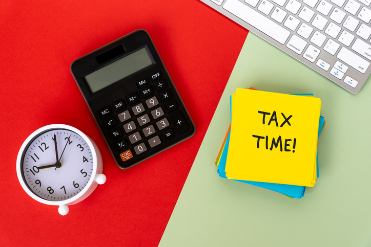 Tax Time on Paper Note With Calculator, Computer Keyboard and Alarm Clock On Red and Green Background