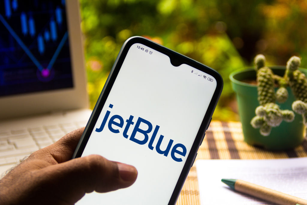 In this photo illustration the JetBlue Airways logo seen...
