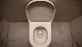 Empty white toilet bowl in a bathroom - Stock photo