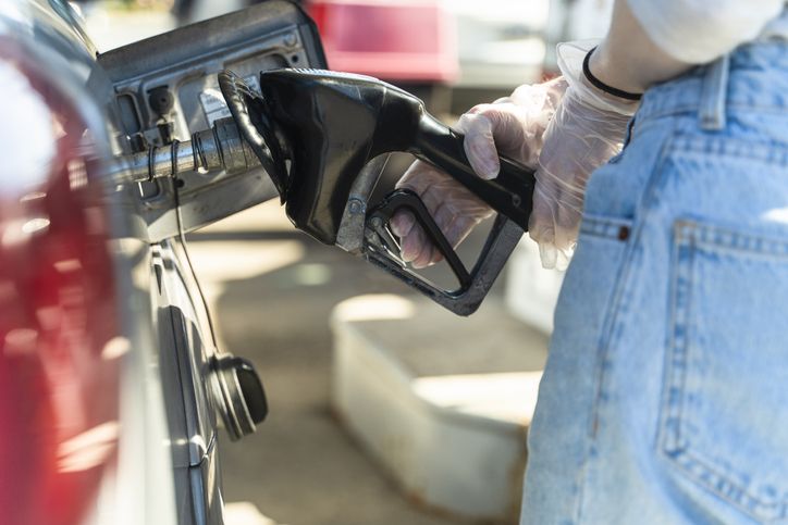 Young Caucasian White long-haired woman refueling a car at the gas station. Close-up view of her hand. She wearing protective latex gloves because of the coronavirus pandemic.