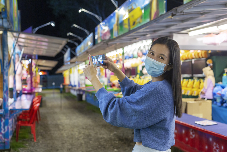 Smiling woman with face mask taking photos at amusement park
