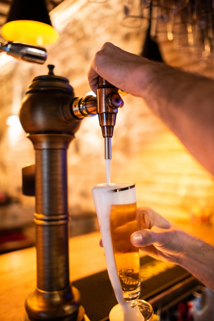 Waiter pulling a mug of beer from tap with foam