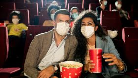Happy couple wearing face masks and enjoying the movie at the cinema