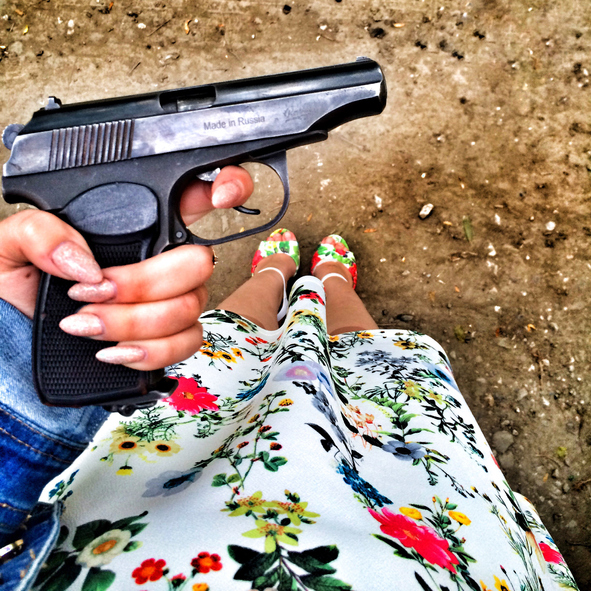 Low Section Of Woman Holding Gun On Land