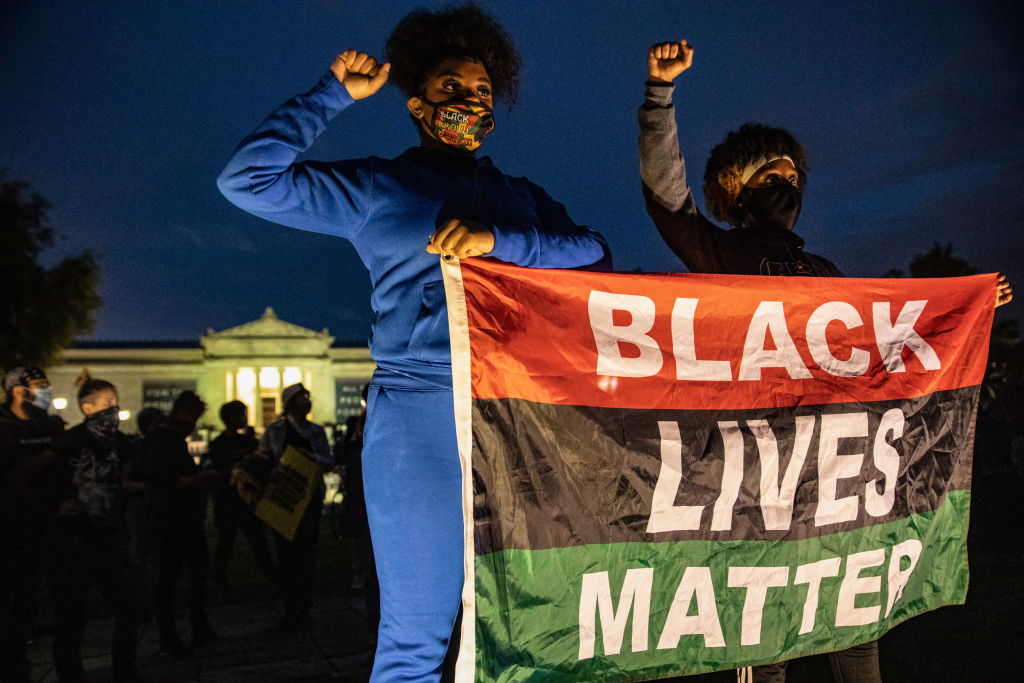 Protesters wearing facemasks stand with a Black Lives Matter...