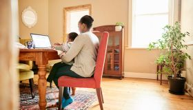 Mother working on a laptop with her daughter sitting on her lap