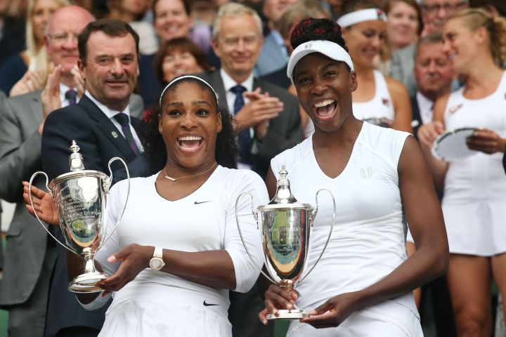 Venus and Serena pose with the winner's trophies at the 2016 Wimbledon Championships