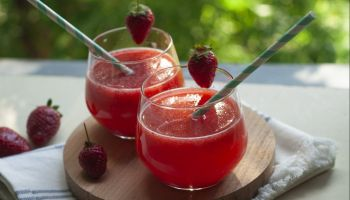 Summer drink: strawberry fruit smoothie in glasses on table over green trees background.