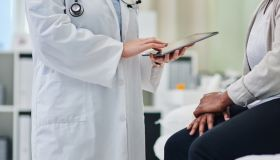 Shot of an unrecognisable doctor using a digital tablet during a consultation with a woman
