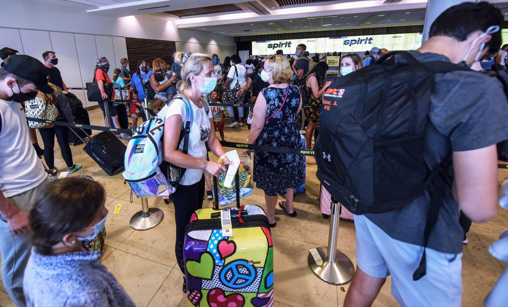 Travelers wait in line to check in at the Spirit Airlines...