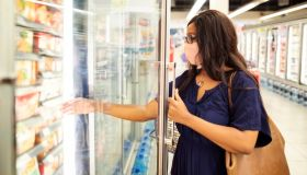 Woman with face mask shopping groceries in supermarket