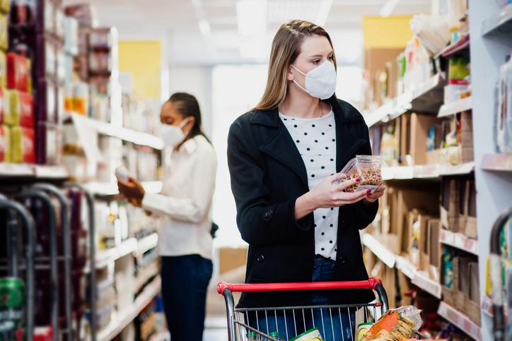 Woman shopping in supermarket wearing coronavirus face mask.