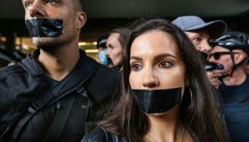 Protesters gather outside Studioworks with black tape on...