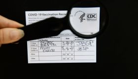 An authentic Covid-19 vaccination card, with CDC logo in magnifying glass